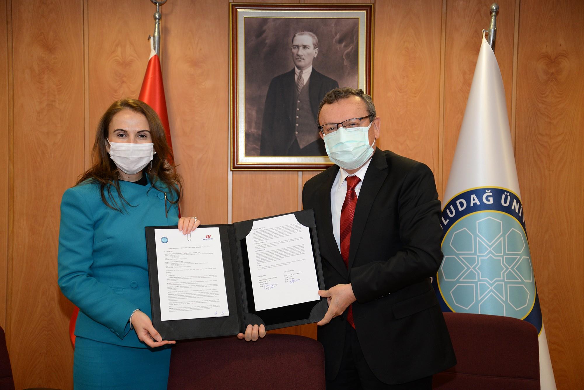 """<p>Bursa Uludağ Üniversitesi'nin (BUÜ), TÜBİTAK 2244 Sanayi Doktora Programı kapsamında firmalarla gerçekleştirdiği protokollere her geçen gün yenisi ekleniyor. Türkiye'nin amortisör üretimi yapan ilk şirketi olan MaysanMando, BUÜ ile 3 doktora öğrencisi için anlaşma imzaladı.</p> <p></p> <p>Bursa'nın önde gelen sanayi kuruluşlarından MaysanMando, TÜBİTAK 2244 Sanayi Doktora Projesi'ne üç doktora öğrencisi ile destek verdi. Protokol imza töreninde BUÜ Rektörü Prof. Dr. Ahmet Saim Kılavuz, MaysanMando Genel Müdürü Tülay Hacıoğlu Şengül ile fakülte ve enstitü yöneticileri hazır bulundu. Törende konuşan Rektör Prof. Dr. Ahmet Saim Kılavuz, """"Bu projeyi oldukça önemli buluyoruz. Bursa'nın, Türk sanayi ve ekonomisindeki yeri ile üniversitemizin eğitimdeki yeri ve konumunu mukayese ettiğimizde bizim bu proje içerisinde olabildiğince fazla yer almamız gerektiğine inandık. Üniversite-Sanayi işbirliğinde ciddi bir mesafe aldık. Bizim yetiştireceğimiz öğrenciler, sizin belirleyeceğiniz problemlere çözüm üreterek, öncelikle üniversiteye, sonra size, son olarak da kentimize ve ülkemize katma değer oluşturacak projeler üretecekler. Nihayetinde Bursa'nın ve ülkemizin kazanacağını düşünüyoruz. Bu projede bizimle işbirliği yapan ve paydaşımız olan MaysanMando firmasına ve yetkililerine teşekkür ediyoruz"""" dedi.</p> <p></p> <p>MaysanMando Genel Müdürü Tülay Hacıoğlu Şengül ise son 20 yılda Türkiye otomotiv endüstrisinin ciddi bir ilerleme kaydettiğini vurguladı. Daha önce sadece üretim ve montaj faaliyetlerine ağırlık verildiğine işaret eden Tülay Hacıoğlu Şengül; """"Özellikle son 10 yıla baktığımızda artık tasarım merkezi haline de geldik. Sanayimizin gelişmesi için sadece üretim yapan değil, gelişime açık ürünler tasarlayan grupta olmamız lazım. Otomotiv endüstrisi hem bir gelişim hem de bir dönüşümün içerisinde. Otomotiv dediğimiz kavram artık değişiyor. Üretim konusunda çok fazla rakibimiz var. Ar-Ge yeteneklerimizle biz eğer nihai ürüne fark oluşturabilecek bir şeyler dâhil edebili"""