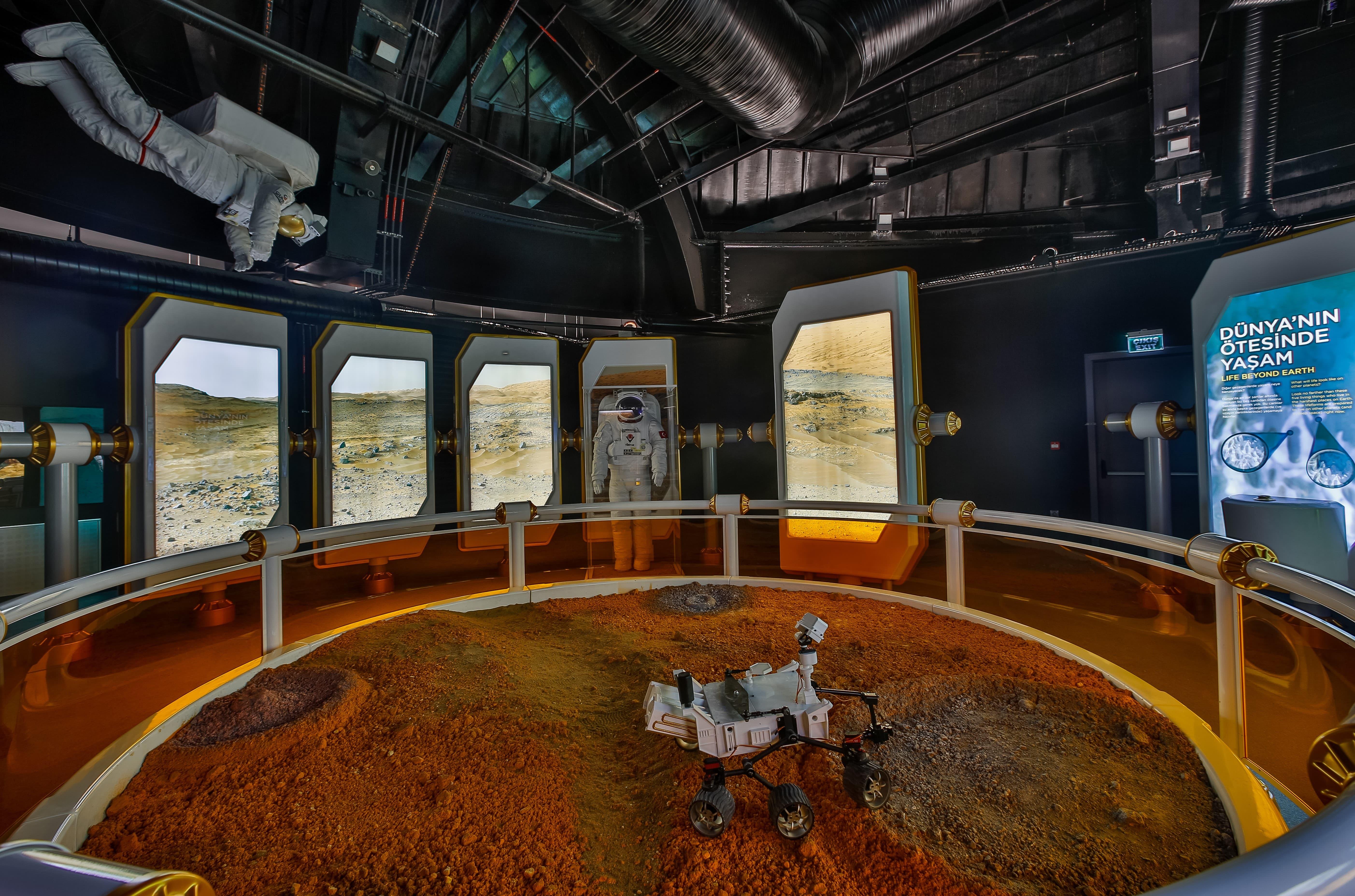 <p>Bursa Ticaret ve Sanayi Odası (BTSO) liderliğinde uzay ve havacılık konusunda heyecan ve farkındalık oluşturmak amacıyla kurulan Gökmen Uzay ve Havacılık Eğitim Merkezi (GUHEM), ziyaretçilerini uzayın derinliklerine götürüyor.</p> <p></p> <p>BTSO öncülüğünde Büyükşehir Belediyesi ve TÜBİTAK işbirliğiyle 13 bin 500 metrekare alanda kurulan, 154 interaktif düzenek ve çeşitli simülatörlerin bulunduğu merkezde ziyaretçilere aya dokunma, ayda yürüme ve uzaya fırlatılma hissi yaşatılmaya çalışılıyor. Zeplin şeklindeki binanın ilk katında havacılıkla ilgili düzenekler, uçak simülatörleri, gerçek boyutlu A-320 uçak modeli, uzay aracı izlenimi verilmiş bir asansörle çıkılan ikinci katta ise gök bilimine dair düzenekler, atmosfer olayları, güneş sistemi, diğer gezegenlerde hayat olasılığı, uluslararası uzay istasyonunda yaşam ve uzaya ilişkin bilgiler sunuluyor.</p> <p></p> <p><strong>UÇUŞ RÜYASI VE UZAYIN KEŞFİ</strong></p> <p></p> <p>Uçuş Rüyası ve Uzayın Keşfi, Model Uçak Uçurun, Pervaneler Nasıl Çalışır, Piston Motoru ve Jet Motoru, Bir Uzay Gezgini Programla, Mars'taki Robotlar, Roket Modelleri, Merkür Programı Fırlatma Deneyimi, Vostok1 Kumanda Modülü gibi daha pek çok deney düzeneğinin yer aldığı merkez, ziyaretçilerine ilginç deneyimler yaşatacak. Yapımı tamamlanan ve resmi açılış töreni, Sanayi ve Teknoloji Bakanı Mustafa Varank'ın katılımıyla 30 Ekim'de gerçekleştirilen merkez, tanıtım amacıyla düzenlenen organizasyonda salgın tedbirleri eşliğinde az sayıda çocuğu konuk etti. Merkez, COVID-19 tedbirleri altında yakın zamanda ziyaretçilerini küçük gruplar halinde düzenli olarak ağırlayacak.</p> <p></p> <p>Mimarisiyle dikkati çeken, uluslararası jüri kurulu tarafından bugünün ve geleceğin en iyi yapılarının seçildiği 2019 Avrupa Gayrimenkul Ödülleri'nde (European Property Awards 2019) Kamusal Yapılar kategorisinde ödül alan merkez, Avrupa'nın en iyi, dünyanın ise en iyi 5 merkezinden biri olarak hayata geçirildi.</p> <p></p> <p><strong>MİLLİ TEKNOLOJİ GÜÇLÜ SANAYİ<
